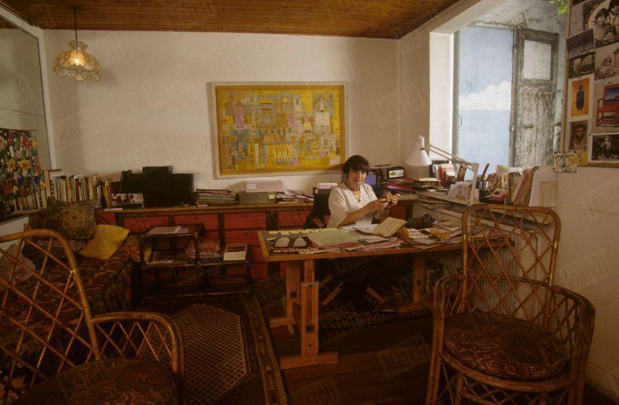 Agnès Varda dans son atelier qui est aussi son refuge; au mur, un tableau de son oncle Yanco.