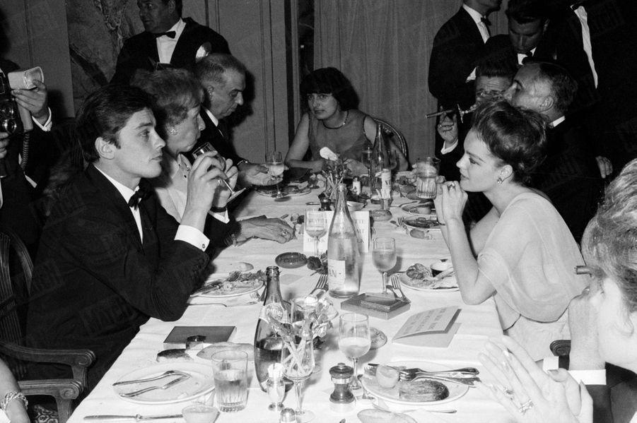 """Alain Delon avec Romy Schneider au Festival de Cannes, en mai 1962. Présidant cette belle table, la réalisatriceAgnès Vardaest en compétition avec son film """"Cléo de 5 à 7""""."""