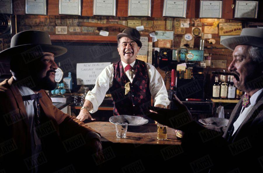 """« En melon 1900, entre deux client également """"d'époque"""". Paul, le barman de l'Auberge de la pépite. Cette pépite, qu'il porte en sautoir, rappelle les temps fabuleux » - Paris Match n°1063, 20 septembre 1969."""
