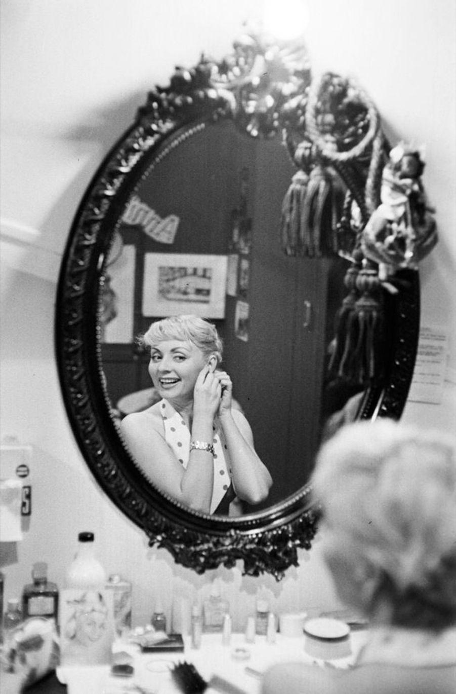 """Annie Cordy dans sa loge du Théâtre de l'ABC à Paris, avant une représentation de l'opérette """"Tête de linotte», en décembre 1957."""