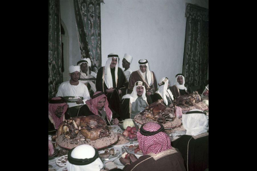 Le roi Saoud Ben Abdel Aziz déjeunant chez l'émir de Riyad avec d'autres invités à qui l'on sert des moutons entiers