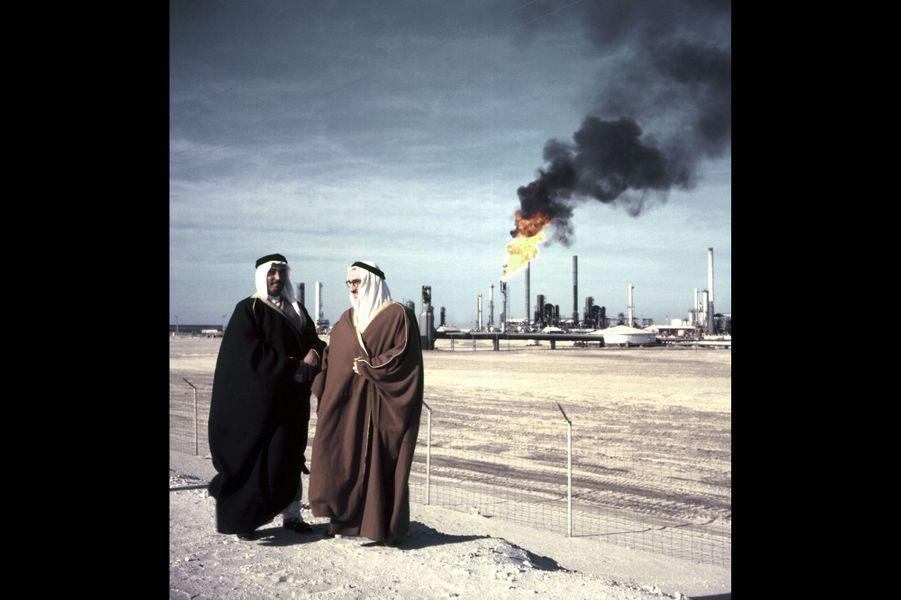 Salih Aloujechan, émir du Ras Tannura, posant avec un homme non identifié devant une raffinerie géante