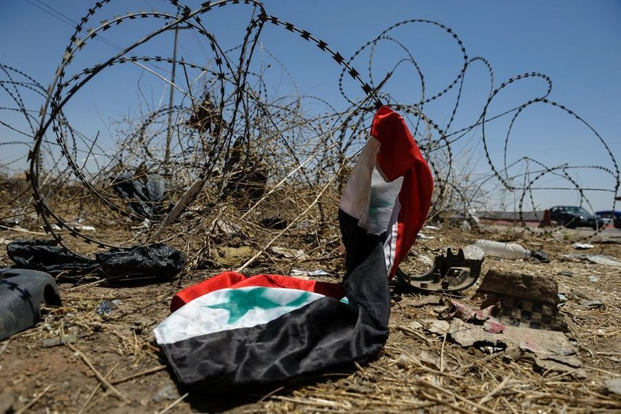 Un drapeau Irakien sur des barbelés au checkpoint de l'entrée EST de la ville de Mossoul. Les soldats de l'armée irakienne y ont abandonné leur matériel et leurs uniformes pour fuir les combattants insurgés de l'EIIL.