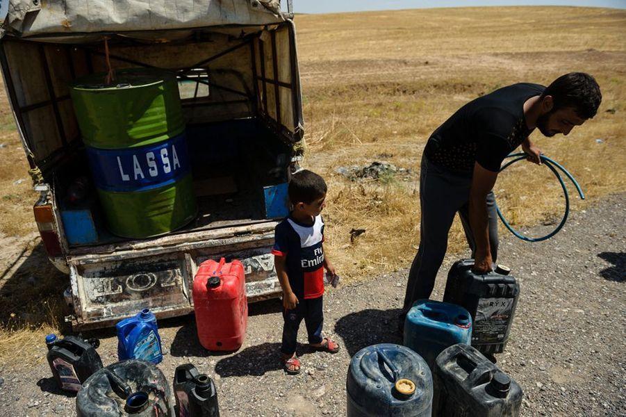Des habitants de Mossoul se ravitaillent en carburant a la sortie Est de la ville en raison des pénuries frappant la ville depuis sa prise par les insurgés de l'EIIL.