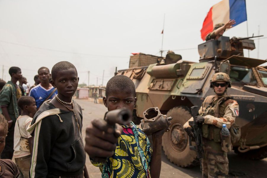 En mars 2013, la prise du pouvoir à Bangui par les milices musulmanes du Seleka s'est accompagnée d'un cortège de 2 000 morts et d'un million de déplacés. Un an plus tard, les ex-victimes se sont muées en bourreaux. Pour les anti-balaka chrétiens, la soif de vengeance semble inextinguible. Ni la présidente, Catherine Samba-Panza, ni les 1 600 soldats de l'opération Sangaris, ne calment le jeu. Le 15 février, Jean-Yves Le Drian, le ministre de la Défense, a annoncé un renfort de 400 hommes, précisant que « ça sera plus long que prévu parce que le niveau de haine et de violence est plus important qu'on imaginait ».Ci-dessus: Lundi 17 février, des gamins des rues jouent aux guerriers autour d'un véhicule blindé de l'opération Sangaris.