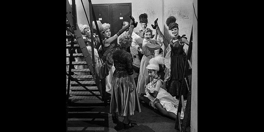 Un jour en France - 1954 – Line Renaud a préféré le Moulin Rouge à trois autres music-hall où elle a commencé son nouveau tour de chant. Ici dans les coulisses, entourée par les danseuses du Moulin.Retrouvez Paris Match Vintage surFacebook,TwitteretInstagram