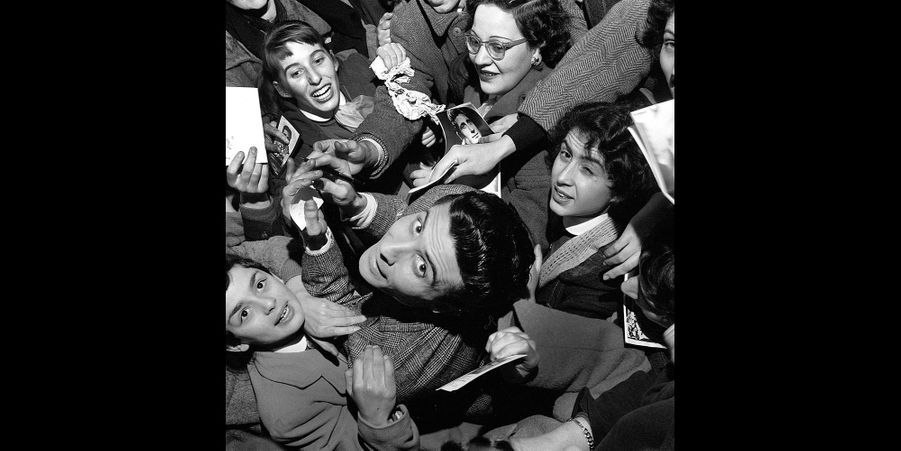 """1956 - Gilbert Bécaud revient des USA. Il a retrouvé à l'Olympia outre son public habituel, 900 fidèles en uniforme: les """"Bécotistes"""". Les filles portent la robe rouge, le corsage bleu, la cravate blanche. Les garçons, le costume bleu, la chemise blanche, le gilet rouge. Leur uniforme leur donne un droit: l'entrée gratuite.Et un devoir : vouer à l'idole un culte tonitruant.Retrouvez Paris Match Vintage surFacebook,TwitteretInstagram"""