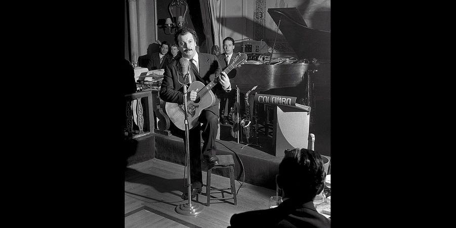 """L'année 1953 marque les débuts de Brassens comme ici dans un cabaret parisien sur les Champs-Élysées. À sa mort en 1981, Roger Therond le directeur de Paris Match, """"copain d'enfance """"de Brassens dans le quartier Haut de Sète, lui rendait un hommage dans le magazine. Dont voici quelques extraits: """"Je t'ai revu à Paris, plus violent qu'avant, vrai anar du libertaire, dans les années 45-56, où tu traînais misère, réfugié chez Jeanne, tu écrivais, tu écrivais. Ton rythme, disais-tu, faisait naître les poèmes. C'était ta technique. C'est chefs-d'œuvre tu les ciselais pour toi seul. Un soir de 1953 où je présentais Brassens à Patachou, tout changea puisque ces chansons privées allaient devenir celles de tous. Quand Patachou l'eut écouté, éblouie par un débutant au talent si mûr, elle me dit, croyant qu' il faisait partie du monde du spectacle: """"À qui appartient-il ?"""" je fus fier de lui répondre: """"À personne!"""" Je compris que Jo , qui avait tant hésité à dévoiler ses chansons comme s'il voulait se préserver de la gloire, risquait de perdre ce pourquoi il était fait : La liberté. Roger Therond.Retrouvez Paris Match Vintage surFacebook,TwitteretInstagram"""