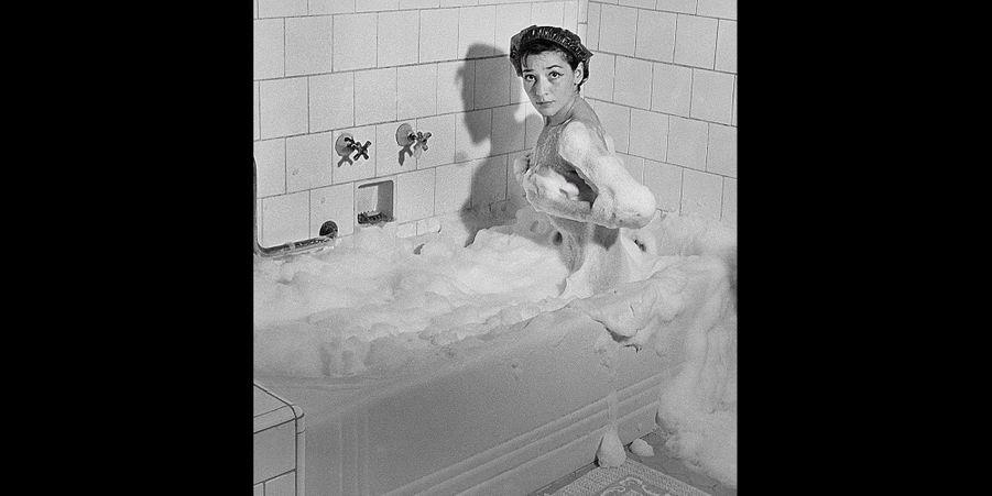 """1951 - Il a fallu huit jours à Juliette Gréco pour conquérir le Brésil. Elle est devenue une vedette à Rio de Janeiro. Elle chantait à Saint-Germain-des-Prés dans le brouhaha d'une cave enfumée. Les Brésiliens l'écoutent religieusement dans le cadre luxueux d'un cabaret au nom français """"La vogue"""". Juliette roule en Cadillac. Chaque matin, le chasseur de l'hôtel dépose à sa porte des corbeilles d'orchidées, des boîtes de bonbons, parfois même des bijoux qu'accompagnent des lettres enflammées. Ici sur la photo Juliette Gréco découvre à Rio la douceur du bain de mousse.Retrouvez Paris Match Vintage surFacebook,TwitteretInstagram"""