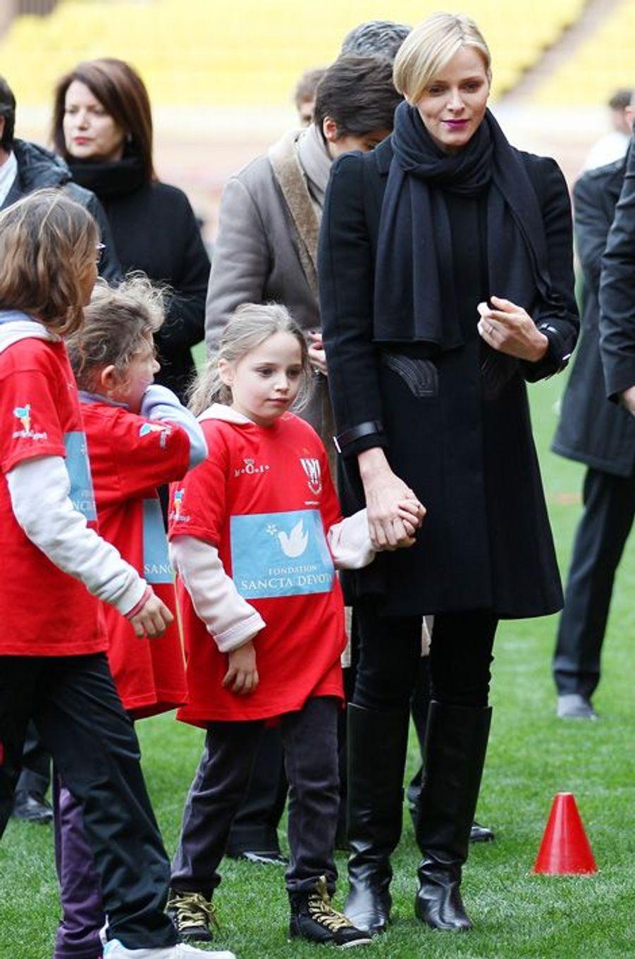 Charlène souriante aux côtés des jeunes rugbymen
