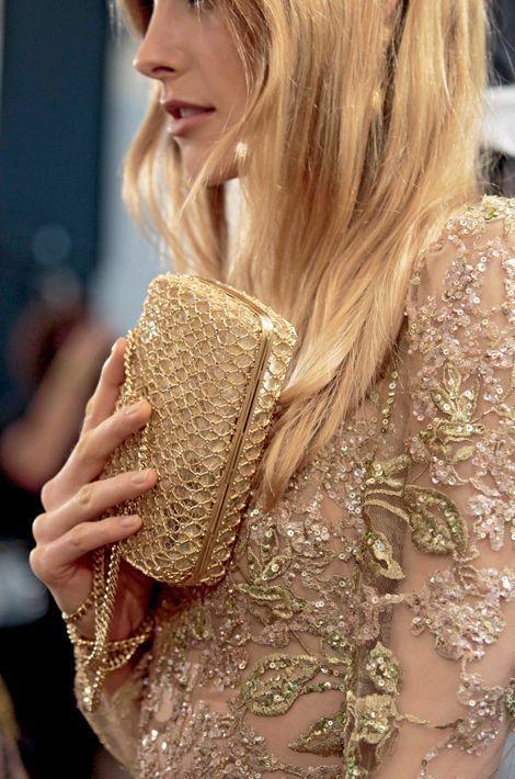 Une minaudière en métal et soie d'or, ultime touche glamour pour accompagner cette robe en guipure de soie à motifs floraux verts et roses, rebrodée de paillettes et de fils d'or. Une ode raffinée aux princesses byzantines.