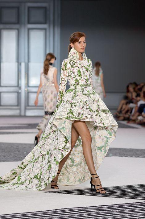 Sa robe en organza brodée à traîne et col rehaussé crée la surprise en se faisant soudain affriolante, dévoilant les jambes. Pour les dix ans de sa maison, le créateur italien, installé à Paris, détourne joliment les codes de la féminité classique. Du grand art.