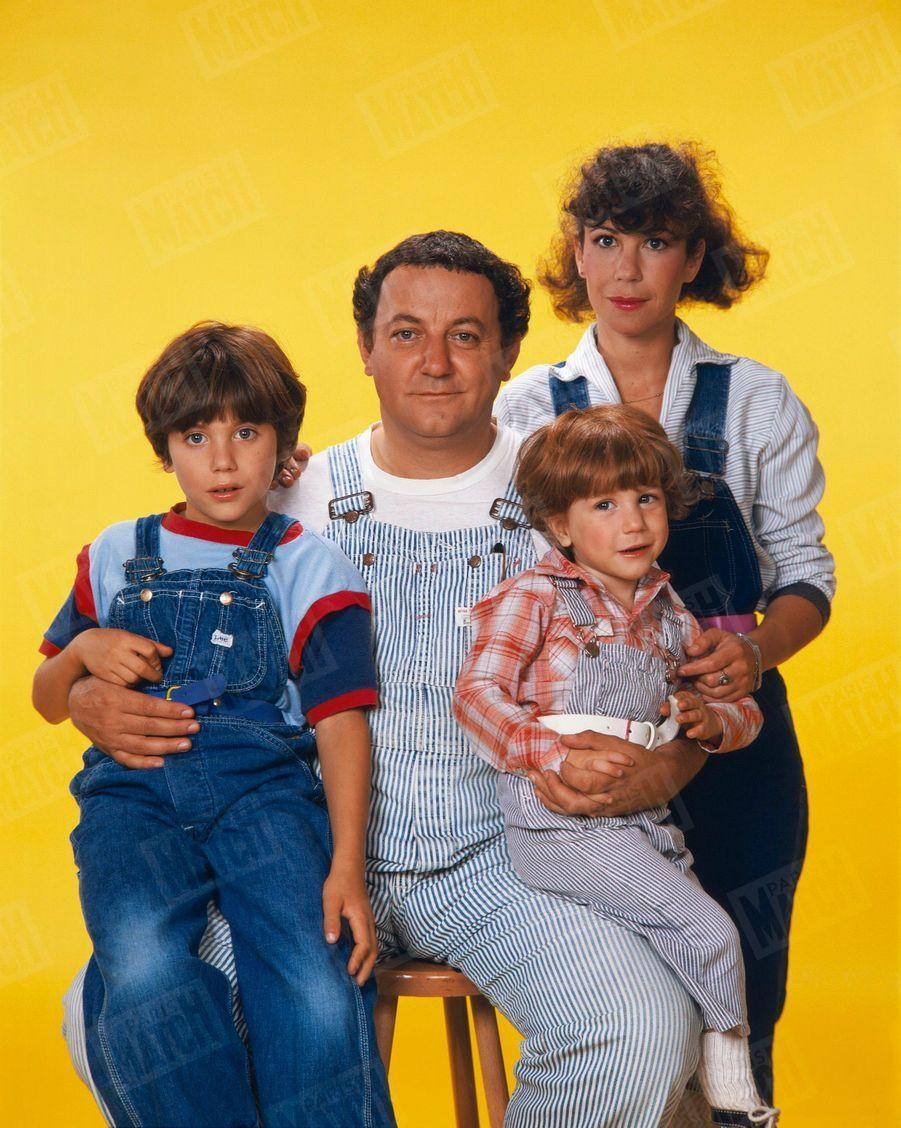 Coluche lors d'une séance photo en famille, avec son épouse Véronique et leurs fils Marius, 4 ans, et Romain, 8 ans, tous en salopette, en octobre 1980.