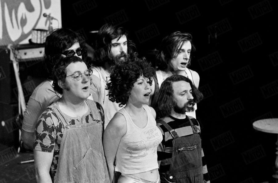 """Coluche avec sa future épouse Véronique Kantor à sa gauche, et leur troupe """"Au vrai chic parisien"""" en décembre 1971."""