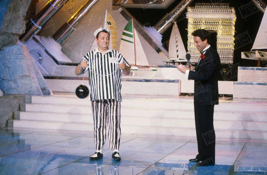 """Coluche aux côtés de Michel Drucker, sur le plateau de l'émission """"Champs-Élysées"""", en juillet 1985."""