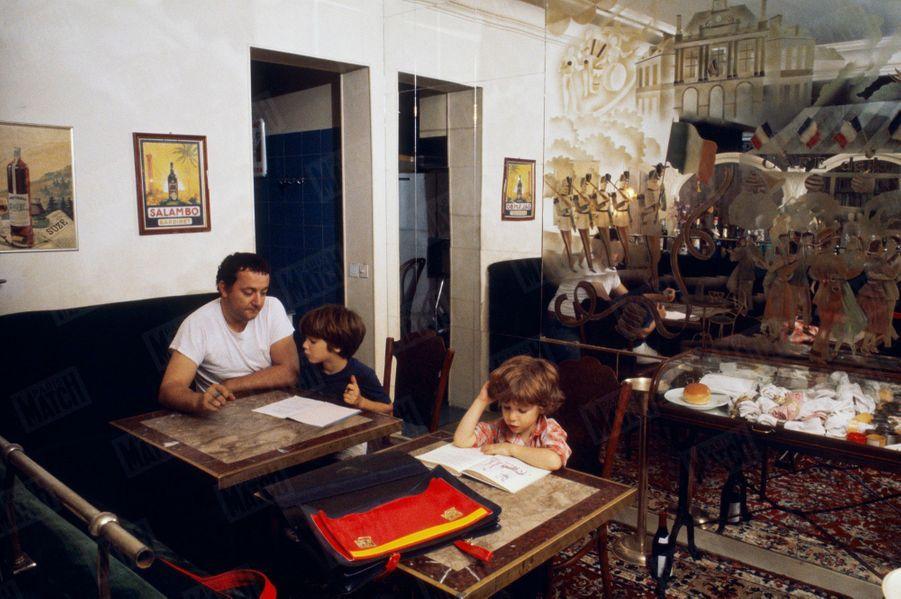 Coluche lors d'une séance photo en famille, avec son épouse Véronique et leurs fils Marius, 4 ans, et Romain, 8 ans, chez eux, rue Gazan, près du parc Montsouris, dans le XIVe arrondissement de Paris, en octobre 1980.