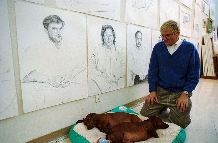 """""""Dans son atelier, David Hockney avec Stanley et Boodgie, et, en arrière-plan, les portraits de ses amis. Chaque portrait demande deux heures de pose."""" - Paris Match n°2335, 24 février 1994"""