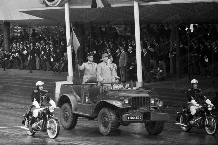 A la tribune, le président Charles de Gaulle assiste au défilé du 14 juillet sur les Champs-Elysées. 1962.