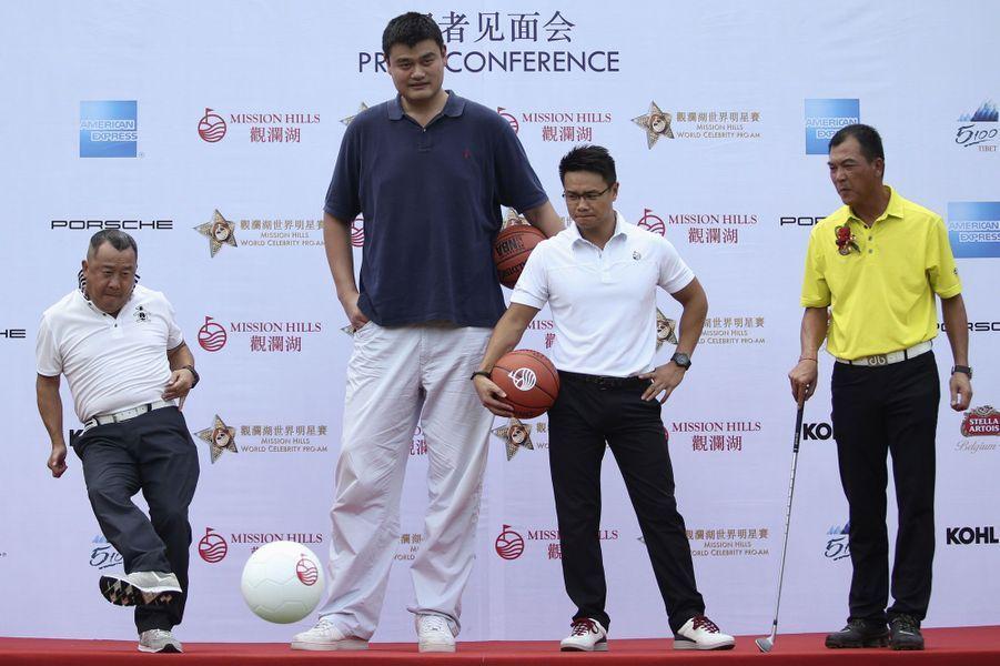 L'acteur Eric Tsang (à gauche) fait quelques passes à l'ancien joueur NBA Yao Ming (au centre) et au joueur de golf Zhang Lianwei lors d'une conférence pour Mission Hills World Celebrity.