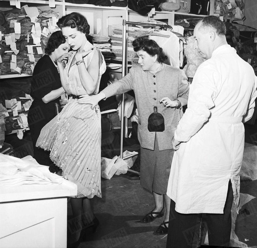 « Cette photo de Christian Dior procédant, en blouse blanche, à un dernier essayage, a été prise mercredi dernier à minuit : dix heures exactement avant la présentation de la collection. » - Paris Match n°47, 11 février 1950