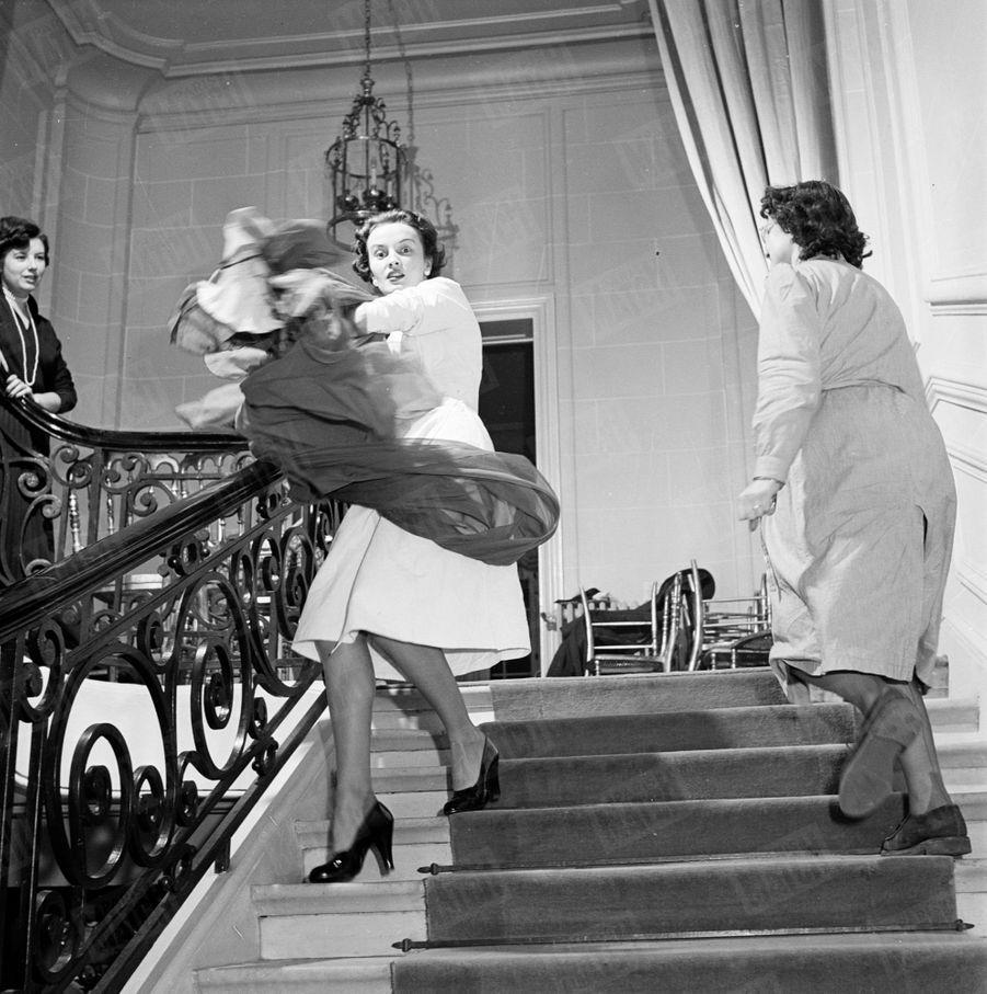Un mannequin descendant les marches de la maison Dior, avenue Montaigne, en février 1950.
