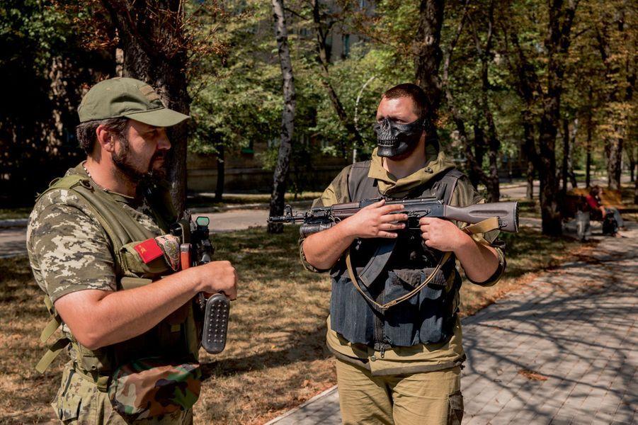 A Yasinovata le 27 août, Piotr Savtchenko (à g.), le vice-commandant du bataillon pro-russe Vostok, avec un de ses hommes portant un masque en forme de tête de mort.