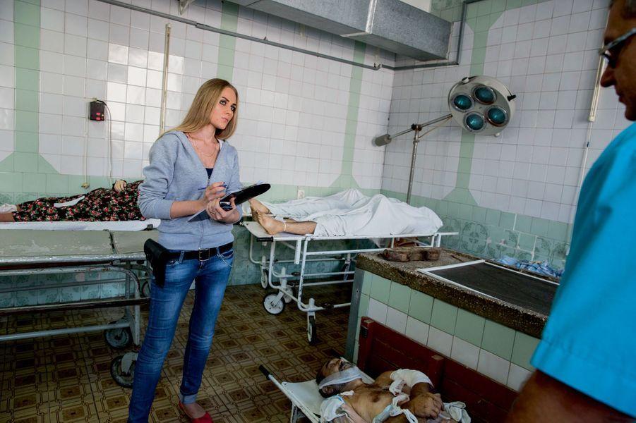 Yelena, 26 ans, de la police de Donetsk, compte les victimes et fait les constatations légales, sur place ou, comme ici le 29 août, à la morgue.