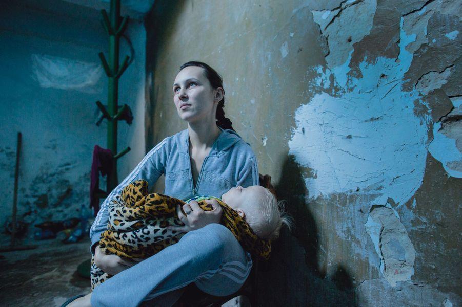 Pour échapper aux miliciens et à la fureur venue du ciel, les gens vivent dans les caves Eugène, Bébé de l'ombre Le 27 août, dans le sous-sol d'un collège de Yasinovata, près de Donetsk. Irina, 33 ans, avec Eugène, son bébé de 11 mois, dont deux passés sous terre, sans eau courante ni électricité.