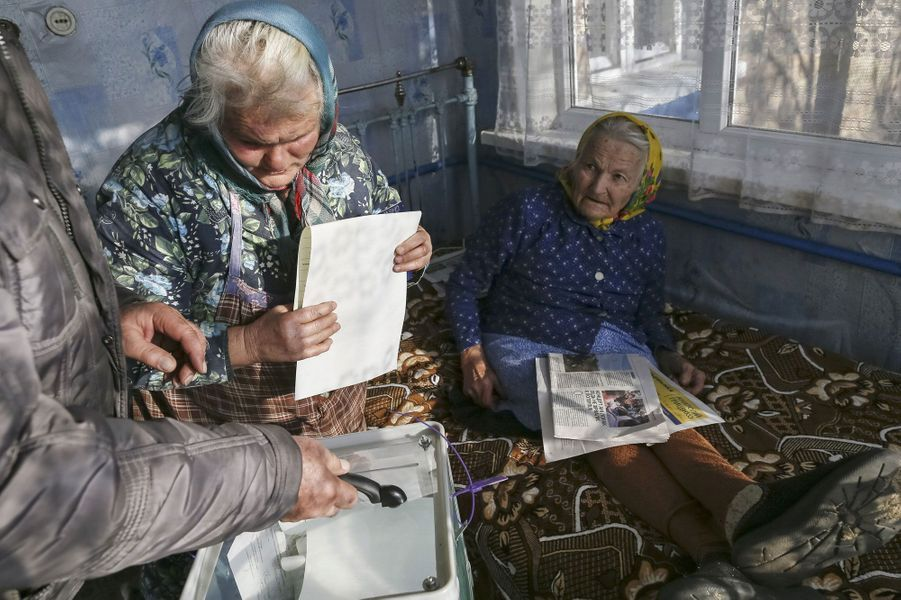 Un membre de la commission électorale rassemble dans une urne mobile les votes des habitants du village deHavronshchyna près de Kiev.