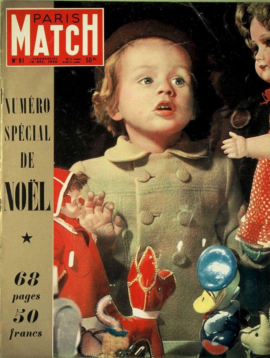 Couverture duParis Match n°91 du 16 décembre 1950 : une petite fille regardant les jouets exposés en vitrine d'un grand magasin parisien.
