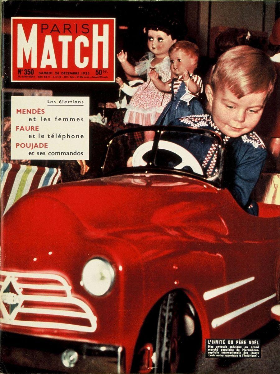 Couverture duParis Matchn°350 du 24 décembre 1955 : un enfant jouant au volant d'une petite voiture rouge au milieu d'autres jouets au marché populaire de Nuremberg.