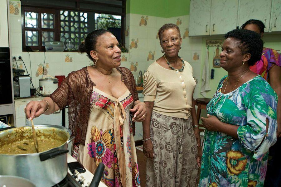 Dès qu'elle arrive, elle défait les tresses qui disciplinent sa coiffure. Peu lui importent le ciel gris, la pluie qui transperce son chapeau de paille. Le portable rangé au fond de son petit panier traditionnel en osier, Christiane Taubira parle créole, marche, fait du vélo tous les jours, encadrée par trois gardes du corps. Après des mois de combat pour faire adopter, contre vents et marées, la loi sur le mariage pour tous, elle respire. En Guyane, le temps des fêtes, madame la ministre retrouve les racines de son originalité, la bohème qui convient à son tempérament nomade. Et sa chère solitude. A nos envoyés spéciaux, elle a confié son rêve : faire bâtir une grande maison bibliothèque, avec un toit en verre pour voir le ciel.Avec ses soeurs Nicole (au centre) et Monique, dans la maison de Montjoly