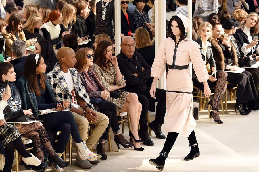 En ce 8 mars, Karl Lagerfeld célèbre la femme au Grand Palais. Chez Chanel, il n'y a que des premiers rangs, la marque a lancé en conséquence sur son compte Instagram le hashtag très malin #FrontRowOnly, repris en masse par les heureux invités du défilé de ce mardi. Parmi eux, le rappeur-producteur Pharrell Williams, la teenage-star et fille de Will Smith Willow accompagnée de sa maman Jada Pinkett Smith, sans oublier la Proud Mama Kris Jenner, venue applaudir sa mannequin de fille. On retrouve dans cette collection les grands classiques de la maison comme le tailleur en tweed mélangé et le chapeau créé par Coco Chanel revisité.A lire aussi: Fashion Week De Rabih Kayrouz à GivenchyKarl n'a de cesse de casser des codes, il intègre cette saison le blouson imperméable bi-matière façon sportswear et l'ensemble sweat-shirt rose pâle à capuche et liserés de cuir porté par Kendall. Des tenues classiques pour des détails beaucoup moins, placés subtilement: la tendance boucle d'oreille unique, les bottes en-dessous du genou bi-matière, les ornements en forme de cœur et tête de chat – clin d'œil à Choupette, la chatte de Karl Lagerfeld reine des réseaux sociaux – et les motifs deux doigts en signe de «peace». Les proportions de cette collection sont juste parfaites, du Chanel chic et classe totalement dans l'air du temps, avec des tenues complètes du matin au soir. Gigi Hadid et sa sœur Bella ont foulé le catwalk de la maison, suivies par les deux garçons chouchou de Karl Lagerfeld: Brad Kroening et Baptiste Giabiconi.A lire aussi: Demna Gvasalia revisite Balenciaga