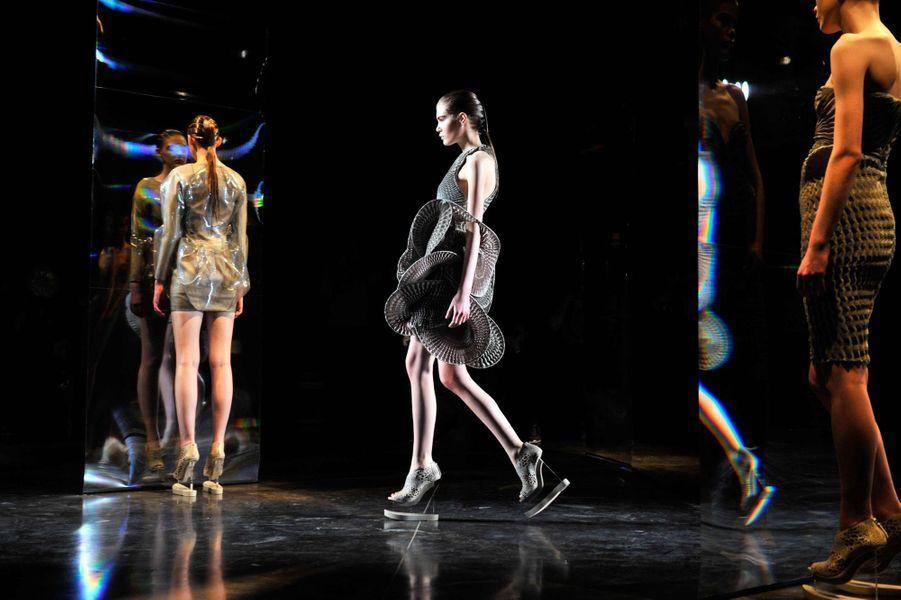 Iris Van Herpen, la féminité à toute épreuve. La créatrice néerlandaise présente une collection de robes uniquement, mais quelles robes! Les matières sont incroyables, les structures complètement folles, l'automne-hiver d'Iris Van Herpen est éblouissant. Une collection futuriste dans la lignée de l'esprit Iris Van Herpen, véritable architecte du 3D dans ses matières. Épaules surélevées, hanches accentuées, ou déconstruction totale façon jupe en reliefs, dans des tons de vert d'eau, bleu nuit et doré. Ses chaussures sont connues pour leur forme et leur talon hors du commun, cette saison ne déroge pas à la règle. Ses plateformes shoes avec Talon au milieu du pied sont déjà un it.