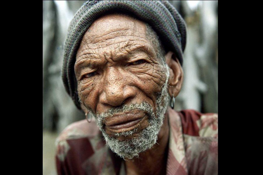 Besa, un chamane bushman, avec ses deux petits-fils. Les Bushmen sont les plus anciens habitants de l'Afrique australe. Au cours des siècles, ce peuple nomade de chasseurs cueilleurs a été décimé par l'arrivée successive des Hottentos et des Bantous qui les ont repoussés vers des terres de plus en plus ingrates, dans le désert du Kalahari. Entre 1997 et 2002, de nombreux Bushmen ont été expulsés de leurs terres de la réserve de gibier du Kalahari central et déportés dans des camps de relocalisation situés en dehors de la réserve. En réaction, les Bushmen intentèrent un procès au gouvernement botswanais et en 2006, avec le soutien de Survival International qui lança une campagne internationale en leur faveur, ils remportèrent une victoire historique en gagnant le droit de retourner chez eux. Cependant, d'autres communautés bushmen sont aujourd'hui menacées d'expulsion dans le cadre du projet de création d'un ʻcorridor écologique'.Nous avons été créés comme le sable, nous sommes nés ici, dit un Bushman. Ce lieu est la terre du père du père de mon père.