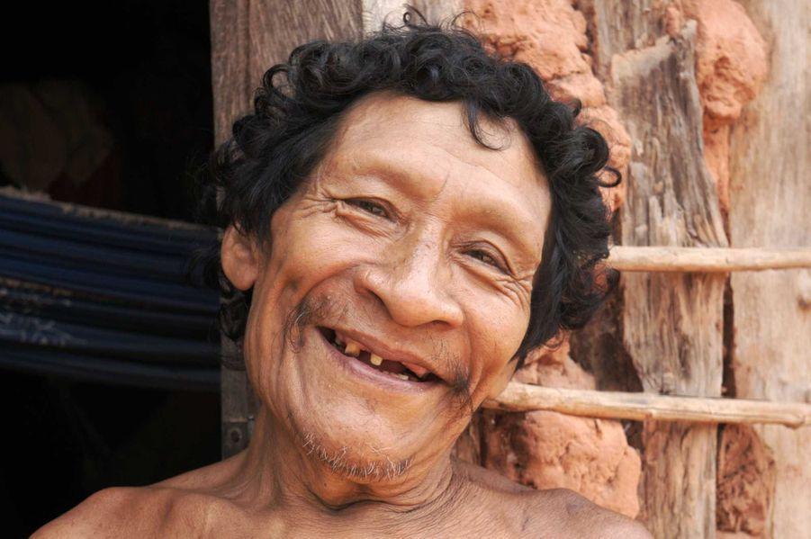 Karapiru, un Indien awá, pose devant sa maison située dans l'Etat brésilien du Maranhão. Son regard trahit le traumatisme qu'il a subi à l'arrivée des envahisseurs de sa terre ancestrale. Après avoir été témoin du massacre d'une grande partie de sa famille par les karai, les non-indiens, Karapiru s'est enfui dans la forêt où il a erré solitaire et constamment sur le qui-vive pendant dix longues années. Quand il a finalement quitté la forêt, les autorités ont fait venir un jeune homme qui parlait sa langue. Un seul mot a instantanément transformé la vie de Karapiru : le jeune homme lui a dit ʻPapa !', parce qu'il était son fils, le seul à avoir miraculeusement survécu au massacre de sa famille.Karapiru est maintenant retourné dans un village awá, mais les problèmes auxquels est confrontée sa tribu sont loin d'être terminés. Leurs forêts disparaissent beaucoup plus rapidement que dans tout autre territoire indigène d'Amazonie brésilienne; les Awá sont considérés comme la tribu la plus menacée au monde.