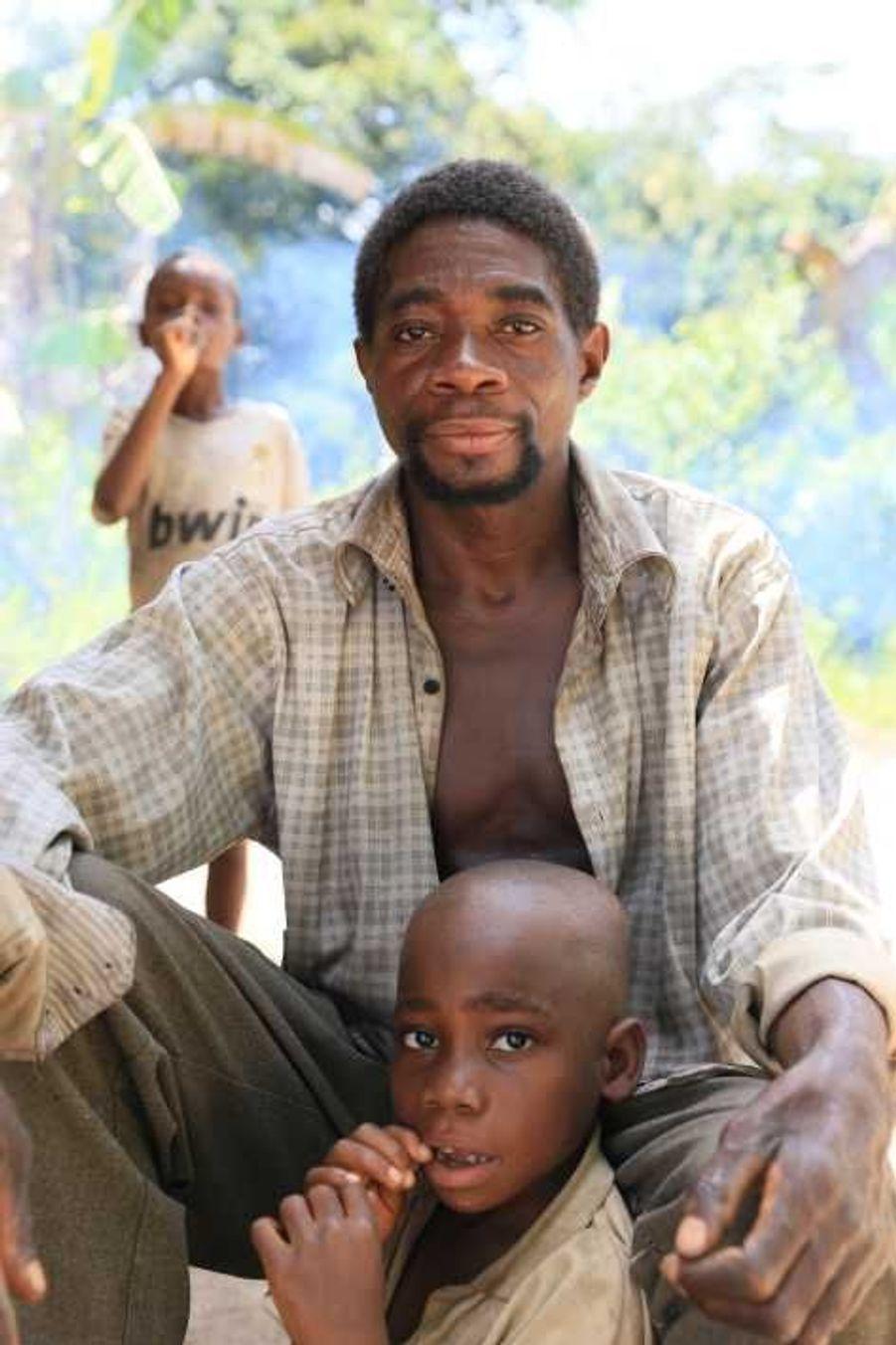 Mongemba et son fils Indongo, Pygmées ba'aka. Parmi les Ba'Aka, qui vivent en République du Congo et en République centrafricaine, les pères passent environ la moitié de la journée auprès de leurs bébés. Ils leur donnent même leur téton à sucer si l'enfant pleure et si la mère, ou une autre femme, n'est pas disponible. Il n'est pas rare de se réveiller dans la nuit et d'entendre un père chantant une berceuse à son enfant, explique le professeur Barry Hewlett, un anthropologue américain qui a vécu avec les Ba'Aka pendant des années. Pendant des décennies, les Pygmées ont été victimes de la spoliation de leurs terres au nom de la conservation et ont souffert des conséquences de l'activité minière, de l'exploitation forestière et du développement des plantations de palmier à huile.Il existe actuellement un projet d'exploitation de mines de fer dans la région de Tridom dans le bassin du Congo. Ce projet nécessitera la construction d'une voie de chemin de fer et occasionnera l'afflux d'un grand nombre d'ouvriers, ce qui affectera encore davantage le mode de vie de milliers de Pygmées baka et bakola.