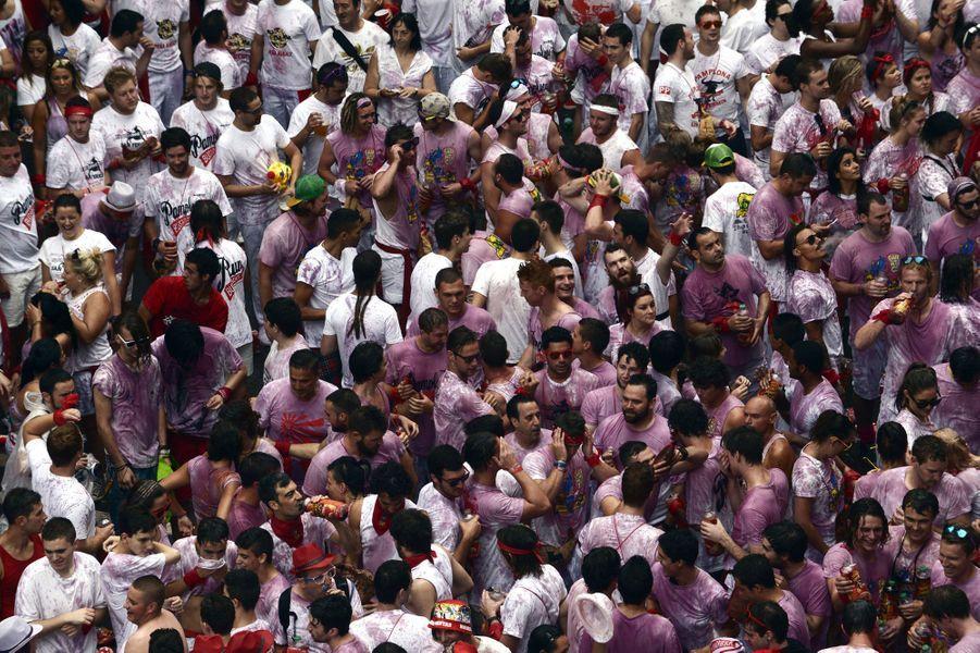 Vêtements blancs -devenus rose avec le vin- et foulard rouge en main, la foule attend impatiemment le «Chupinazo», le coup d'envoi des fêtes de San Fermin.