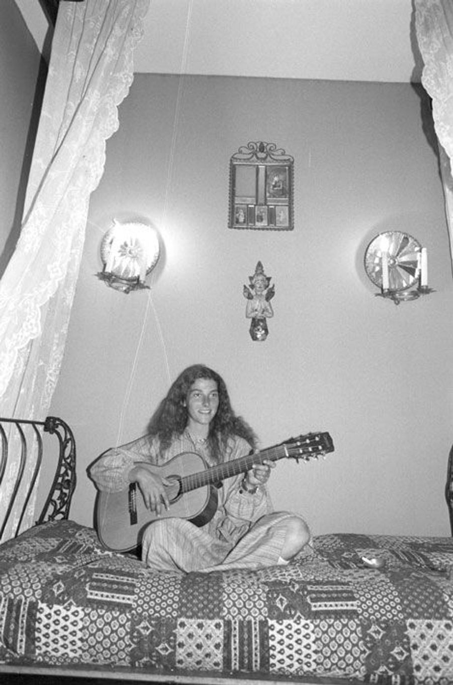 Florence Arthaud chez elle à Paris dans la grande maison familiale, jouant de la guitare assise en tailleur sur son lit à baldaquin dans sa chambre.
