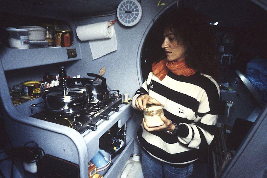 Une conserve à la main, la navigatrice est devant une cuisinière dans la cabine de son trimaran «Groupe Pierre 1er».