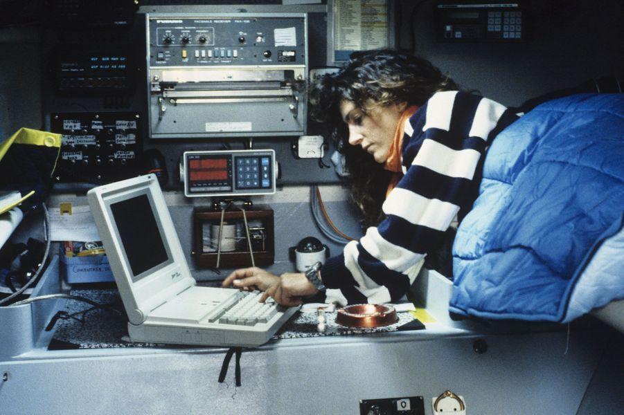 En Angleterre, à Plymouth, le 6 juin 1988, à l'occasion de la Transat Plymouth-Newport, une course de voile, Florence Arthaud pianote sur son matériel de navigation, dans la cabine de son trimaran «Groupe Pierre 1er».