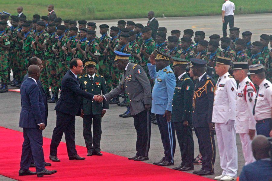 Le chef d'état français salue les haut-gradés ivoiriens alors que l'on aperçoit également les officiers français à la tête de l'opération Licorne.