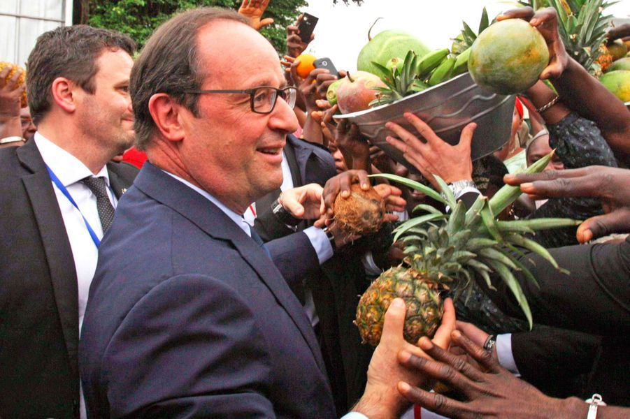 A Abidjan, François Hollande reçoit des fruits en cadeau de la part d'habitants chargés de lui souhaiter la bienvenue.