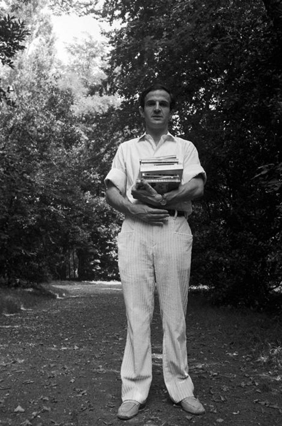 """En Italie, dans le cadre de la 27e édition du festival """"la Mostra de Venise"""" qui s'est déroulée du 28 août au 10 septembre 1966, le réalisateur François TRUFFAUT venu à la Mostra de Venise 1966 pour présenter son film """"Fahrenheit 451"""", posant debout dans un parc avec un pile de livres dans les bras."""