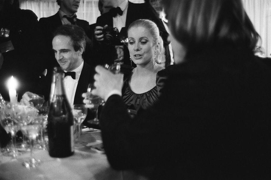"""Catherine DENEUVE souriante (Meilleure actrice pour """"Le dernier métro""""), assise entre François TRUFFAUT (Meilleur réalisateur et meilleur film) et Gérard DEPARDIEU (Meilleur acteur), tous trois à table un verre àla main au dîner donné au Fouquet's à PARIS."""