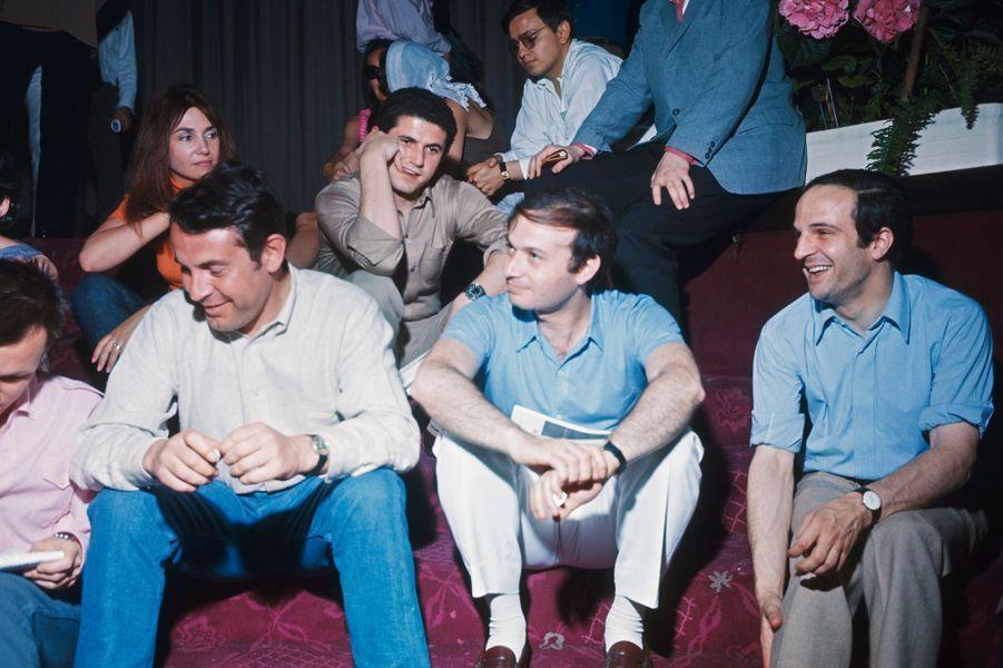 Le 21ème Festival de CANNES 1968 s'arrête. De nombreux cinéastes décrètent l'interruption du festival et occupent la salle : Claude LELOUCH, Claude BERRI , François TRUFFAUT et d'autres personnes assis sur les marches au pied de la scène.