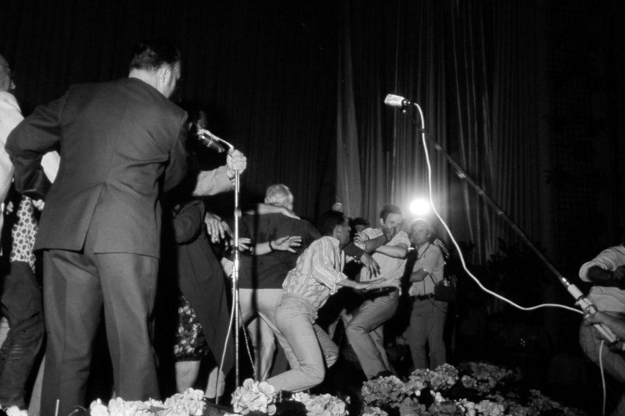 Le 21ème Festival de CANNES 1968 s'arrête. De nombreux cinéastes décrètent l'interruption du festival et occupent la salle : François TRUFFAUT sur scène, reçoit un coup de poing en pleine figure d'un festivalier en colère.