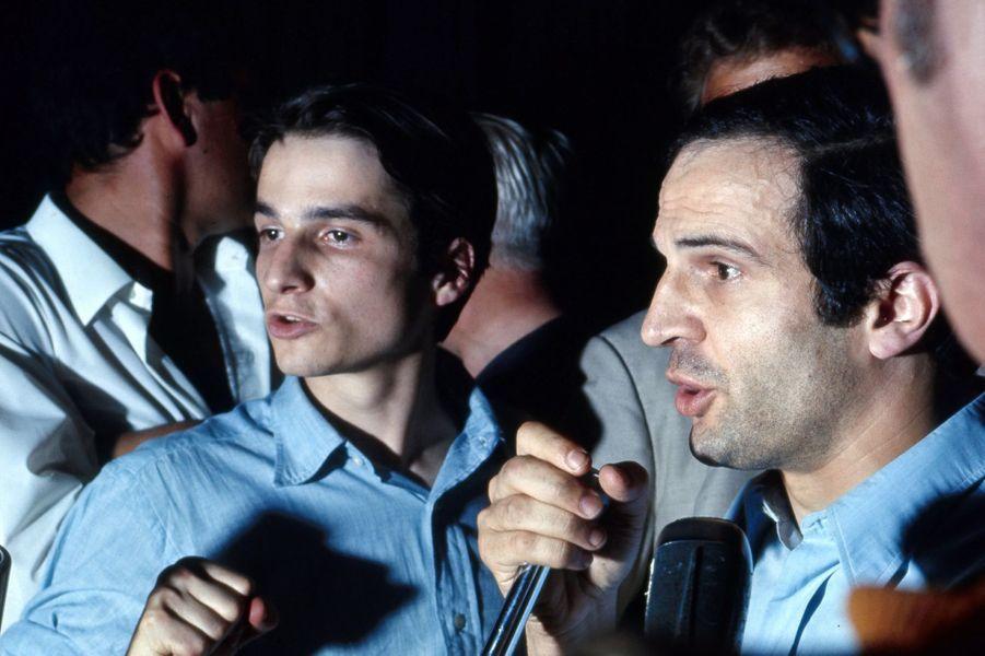 Le 21ème Festival de CANNES 1968 s'arrête. De nombreux cinéastes décrètent l'interruption du festival et occupent la salle : plan de profil de François TRUFFAUT parlant dans un micro aux côtés de Jean-Pierre LEAUD.