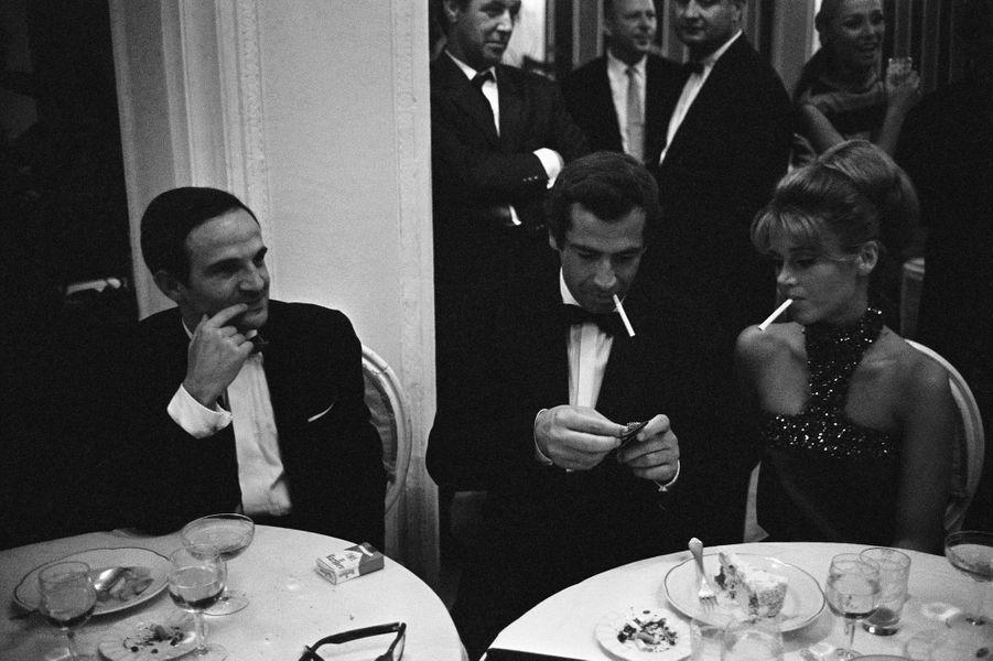 """Mostra de Venise 1966 : venus présenter leur film """"La Curée"""" au festival, Roger VADIM et son épouse Jane FONDA dînant à une table, cigarette à la bouche, François TRUFFAUT, venu promouvoir son film """"Fahrenheit 451"""", assis à leur côté."""