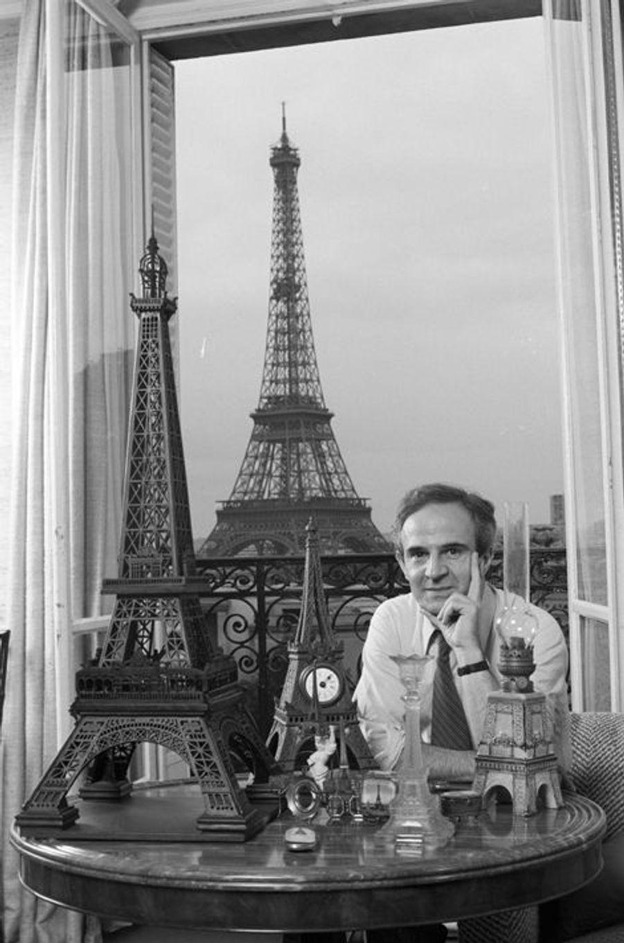 Paris, 12 septembre 1980, dans son appartement avec vue sur la Tour Eiffel, le réalisateur François TRUFFAUT pose avec sa collection d'objets à l'effigie du monument.